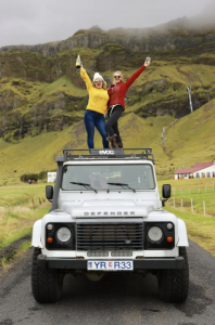 Two woman stnading on top of a car posing for a picture